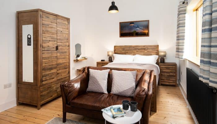 Reiver Studio – Image of bed, sofa, coffee table and wardrobe in a driftwood theme
