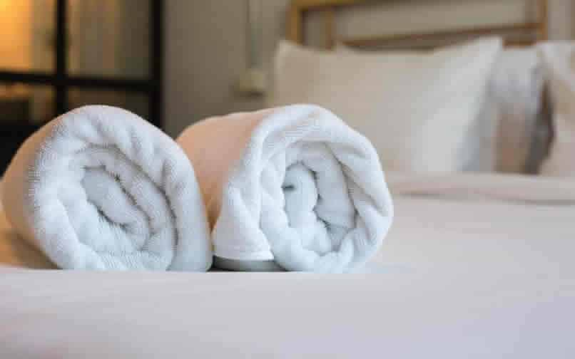 Towels on bed in accommodation