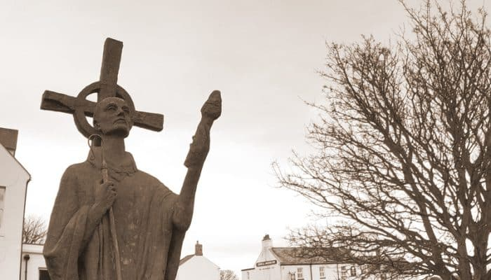 Statue of Saint Aidan of Lindisfarne next to Lindisfarne Priory ruins.